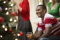 Adults in room around Christmas tree — Stock Photo