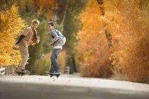 Meninos em pranchas de skate em uma estrada — Fotografia de Stock