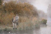 Couple debout sur une berge, pêche. — Photo de stock