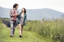 Man and woman walking through a meadow — Stock Photo