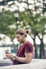 Man in a park checking his cell phone — Stock Photo