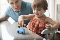 Man and a child playing with toy cars. — Stock Photo