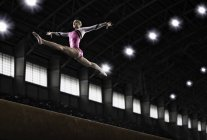 Woman gymnast performing on beam — Stock Photo