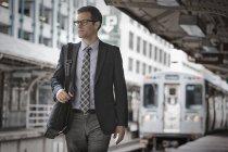 Businessman on a railway station platform. — Stock Photo