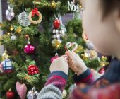 Boy placing Christmas decorations on tree — Stock Photo