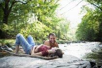 Чоловік і жінка лежить на скелі — стокове фото