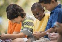 Crianças usando comprimidos e jogos handheld — Fotografia de Stock