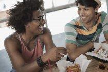 Hombres sentados comiendo en un restaurante - foto de stock