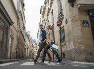 Couple walking along a narrow street — Stock Photo