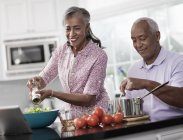 Mature couple in their kitchen — Stock Photo