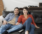 Couple sitting on a sofa and watching tv. — Stock Photo