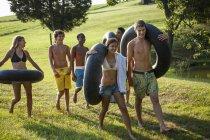 Niños y niñas, con toallas y flotadores de baño - foto de stock