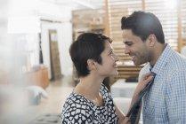 Женщина регулирует мужской галстук — стоковое фото