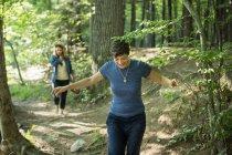 Women walking down woodland path. — Stock Photo