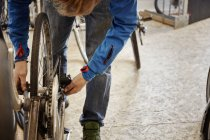 Young man repairing a bicycle. — Stock Photo