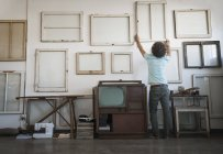 Man hanging framed picture canvases — Stock Photo