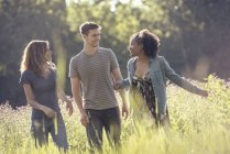 Man and two women walking in a meadow — Stock Photo