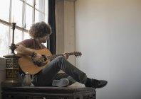 Mann, die Gitarre von einem Fenster sitzen — Stockfoto