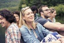 Gruppo di donne e uomini seduti da un lago — Foto stock
