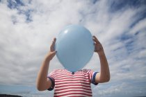 Мальчик, стоящий с воздушным шаром — стоковое фото
