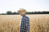 Agricultor em pé num campo de trigo — Fotografia de Stock