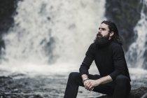 Человек, сидящий у горного ручья . — стоковое фото