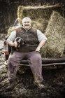 Agricoltore che tiene maialino e sorride — Foto stock
