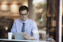 Homme d'affaires utilisant une tablette numérique dans un café . — Photo de stock