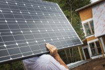 Workman carrying a large solar panel — Stock Photo