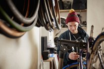 Man repairing a bicycle in cycle shop — Stock Photo