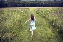 Menina correndo através de um prado — Fotografia de Stock