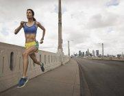 Woman running along an urban road — Stock Photo