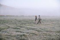 People walking across a meadow — Stock Photo
