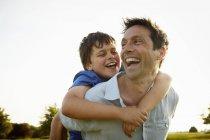 Батько дати синові piggyback. — стокове фото