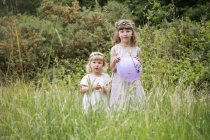 Girls standing in a meadow. — Stock Photo