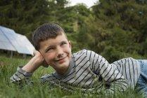 Мальчик, лежащий в траве — стоковое фото