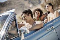 Amigos en un convertible azul pálido - foto de stock