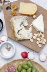 Cheese board with olives and nuts — Stock Photo