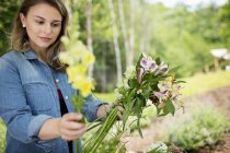 Woman holding summer garden flowers. — Stock Photo