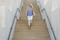 Donna bionda che cammina giù — Foto stock