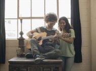 Hombre tocando la guitarra y una mujer con el teléfono - foto de stock