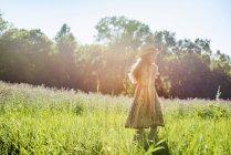 Girl walking in a field in the sunshine — Stock Photo