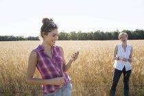 Mulheres de pé em um campo de trigo — Fotografia de Stock