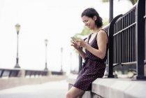 Женщина, проверяя ее сотовый телефон — стоковое фото