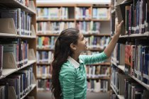 Fille regardant livres — Photo de stock