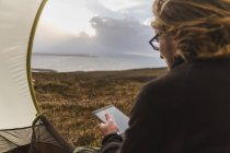 Человек в палатке, держа цифровой планшет — стоковое фото