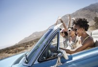 Young people in a pale blue convertible — Stock Photo