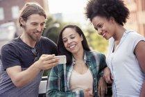 Homme et deux femmes en regardant un téléphone intelligent — Photo de stock