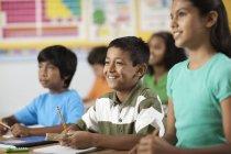Junge Mädchen und Jungen in einem Klassenzimmer — Stockfoto