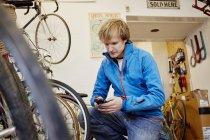 Человек, делая вызов в магазине цикла — стоковое фото